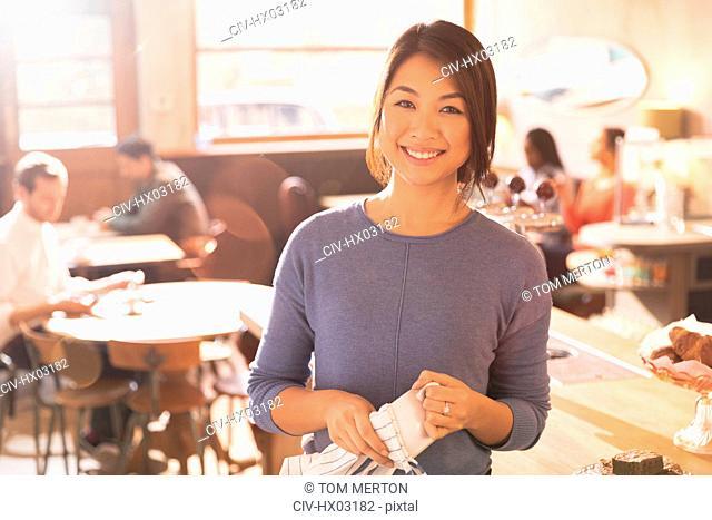 Portrait smiling female barista in cafe