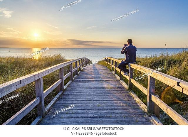 Weissenhäuser Strand, Ostholstein, Schleswig-Holstein, Germany. Man photographing the sunset on a pier to the Baltic Sea