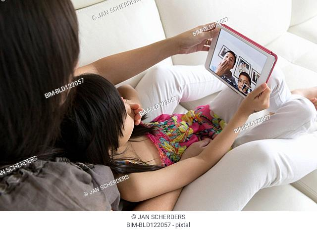 Asian mother and daughter talking to family on digital tablet