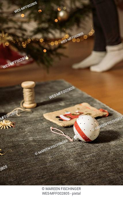 Christmas decoration lying on carpet, woman decorating tree in background