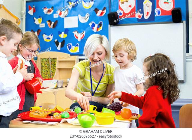 Nursery teacher playing kitchen roleplay with her students in the classroom