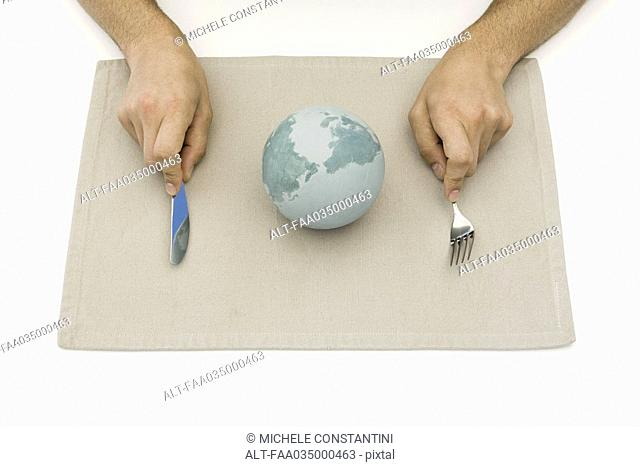 Person sitting before globe on placemat, holding fork and knife, cropped view