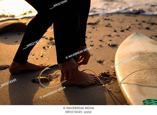 Surfer tying surfboard leash on his leg at beach