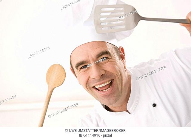 Laughing cook holding a cooking spoon and a ladle