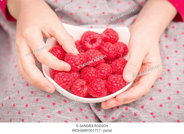 Girl with raspberries in a bowl