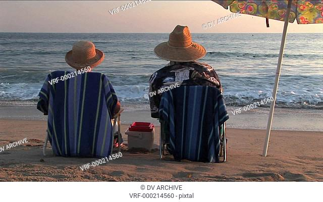 A couple relaxes in beach chairs under an umbrella while watching the ocean