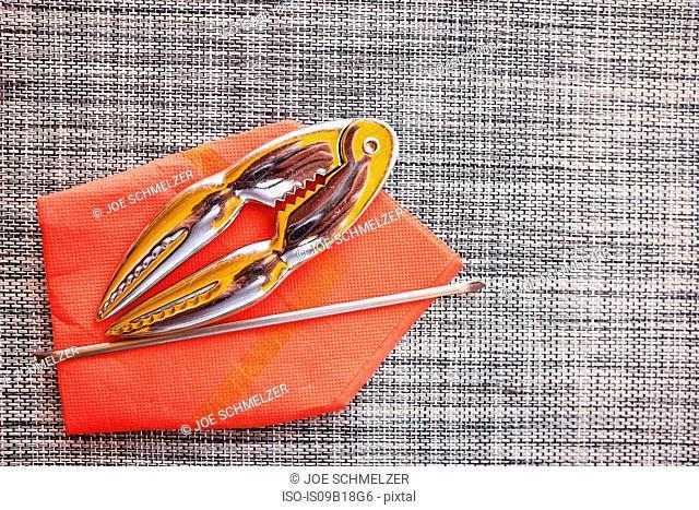 Shellfish cracker, fork, orange napkin on placemat