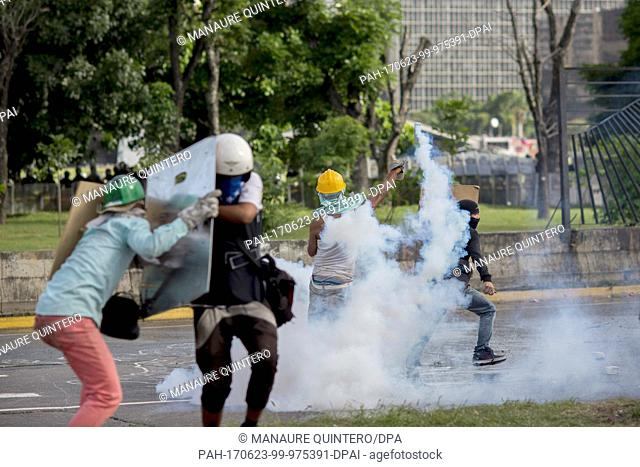 Protesters seek refuge from the tear gas during a protest against the government in Caracas, Venezuela, 23 June 2017. The crisis in Venezuela keeps on...