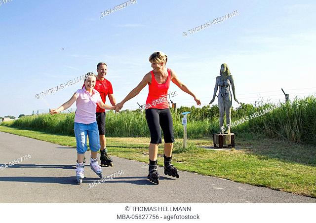 Family is riding Inline skates by the sea
