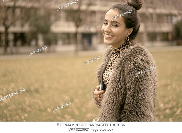 fashionable vibrant woman running outdoors in park, autumn season, wearing coat, happy laughing, candid emotion, walking in city, Munich, Germany