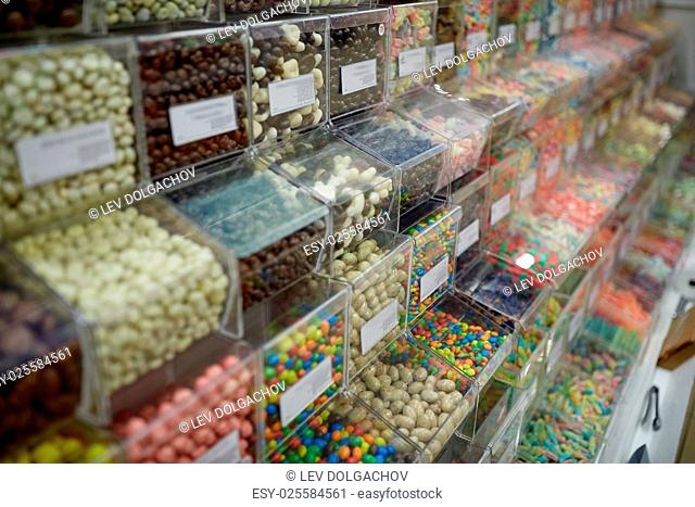 food, junk-food, sell, confectionery and unhealthy eating concept - different sweets in transparent plastic boxes at candy shop