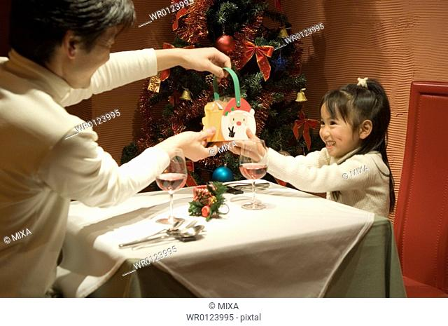 Father giving Christmas present to daughter