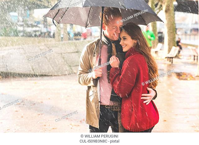 Couple with umbrella, standing under rain in park, London, UK
