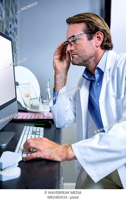 Thoughtful dentist working on computer