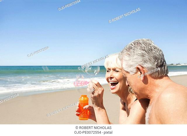 Laughing senior couple blowing bubbles on beach