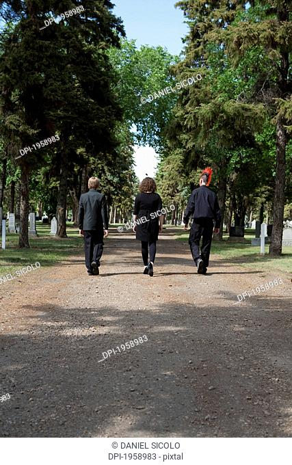 Three Young People Walking Down A Path In A Cemetery; Edmonton, Alberta, Canada