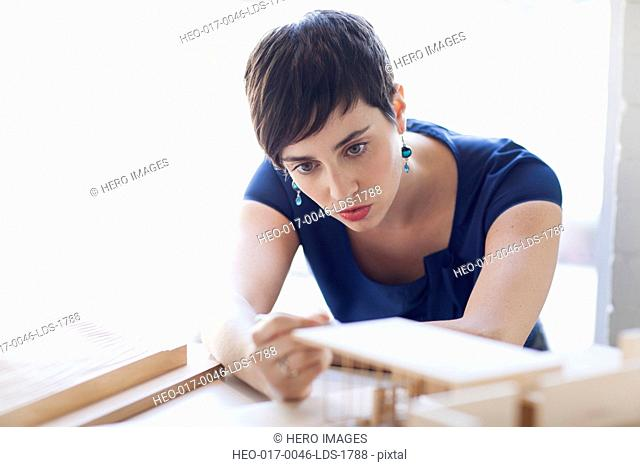 stylish young woman looking at architectural model