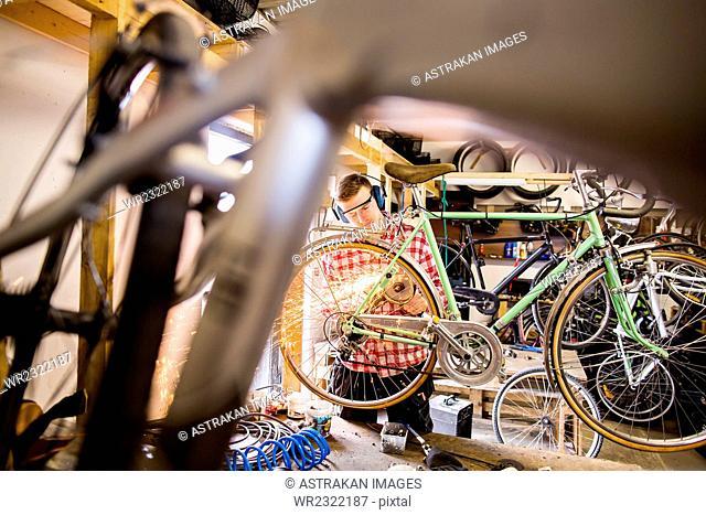 Repairman using welding torch on bicycle in workshop