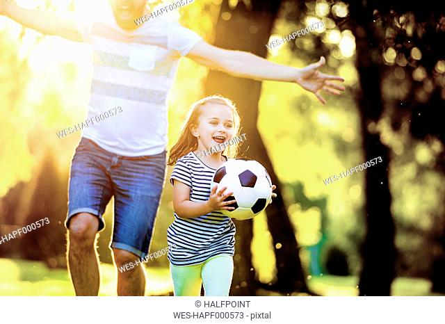 Happy little girl with soccer ball playing with her father in a park