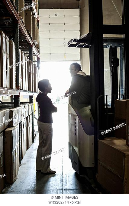 Two warehouse employees talking over an issue while working in a distribution warehouse