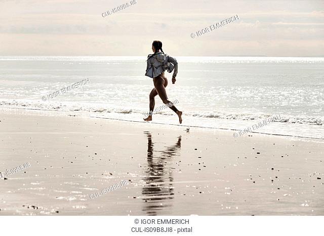 Young female runner running barefoot along water's edge at beach