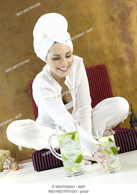 Woman sitting on cushion holding glass of lime water, smiling