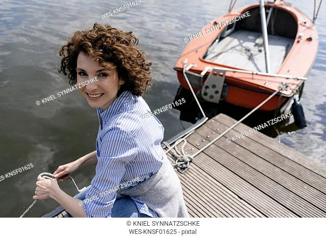 Woman standing on jetty with moored sailing boat