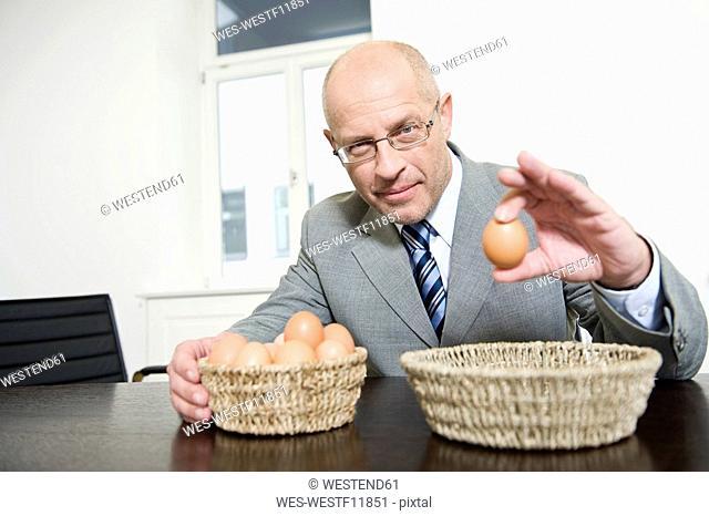 Germany, Munich, Businessman holding an egg, portrait