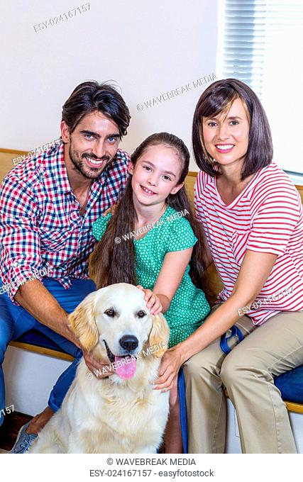 Smiling family sitting and posing with their dog