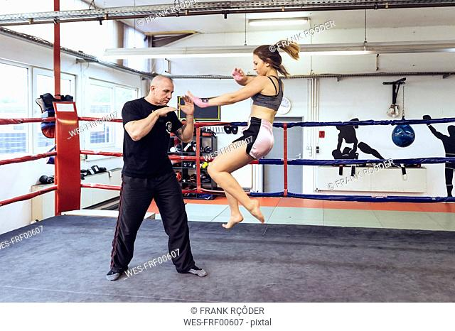 Female martial artist sparring with coach