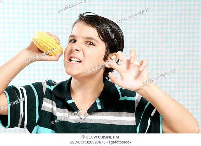 Boy holding a corn cob and looking angry