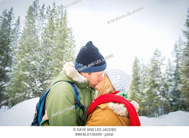 Caucasian couple kissing in snowy forest