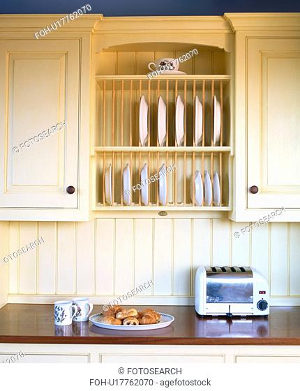Close-up of toaster on worktop below integral plate-rack in cream fitted kitchen cupboard