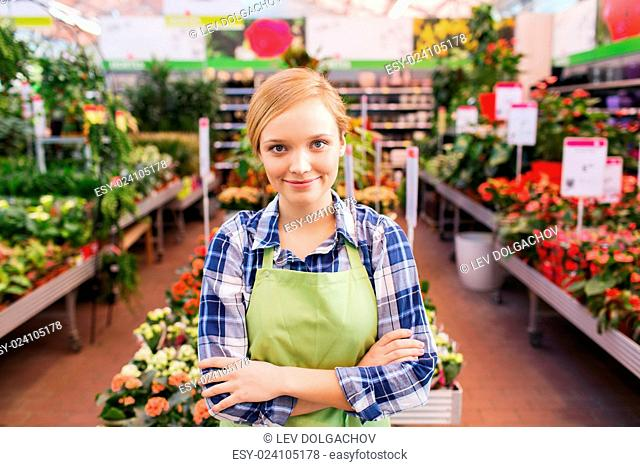 people, gardening and profession concept - happy woman with flowers in greenhouse