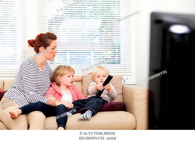 Mother with two children watching television