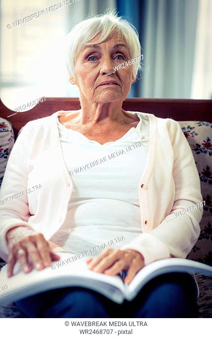 Pensive blind woman sitting on sofa with braille book on lap