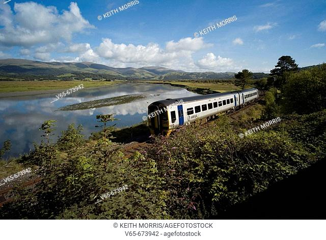 Arriva Trains Wales diesel train at Dovey Junction near Machynlleth Powys, with the Dyfi River behind and the hills and mountains of Snowdonia National Park in...