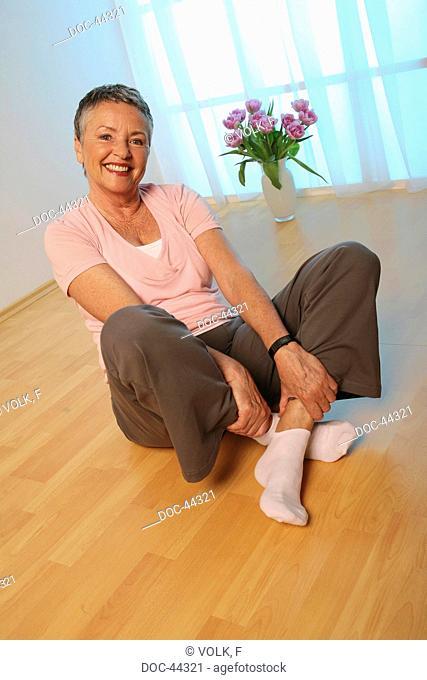 older woman sitting on the floor - doing gymnastics - senior
