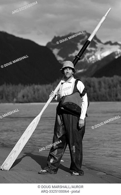 A man stands on the shores of a river for a portrait with an oar, wool hat and rain slicker overalls