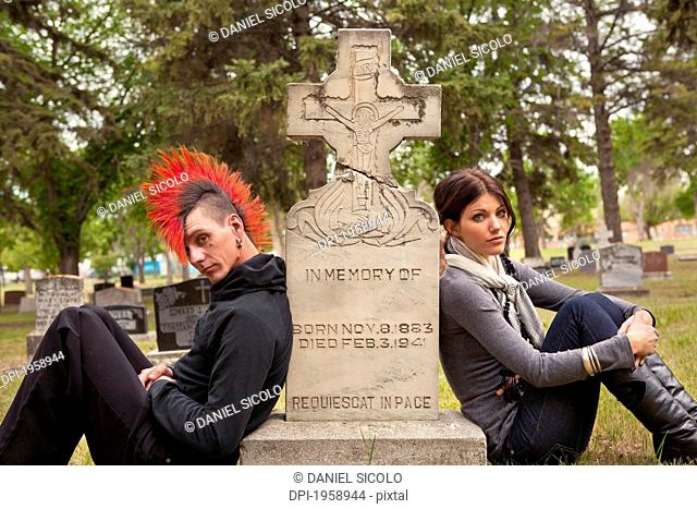 A Young Man And Young Woman Sit Against A Tombstone In A Cemetery; Edmonton, Alberta, Canada