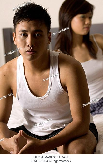 An asian man sits on the edge of the bed with his girlfriend (out of focus) behind him