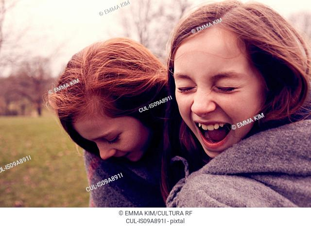 Young friends wrapped in a blanket and laughing outdoors
