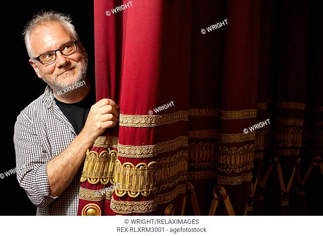 Happy mature man peeking from behind red stage curtain
