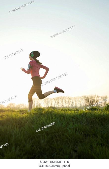 Young female runner listening to headphones whilst running
