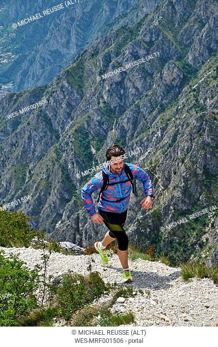 Italy, Trentino, man mountain running near Lake Garda
