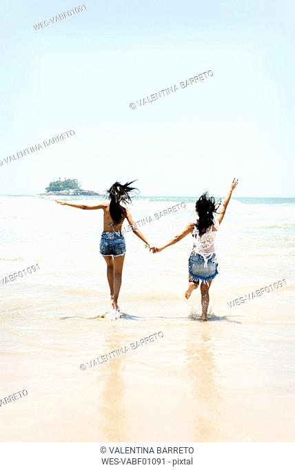 Brasil, Sao Paulo, Ubatuba, two young women running on the beach holding hands
