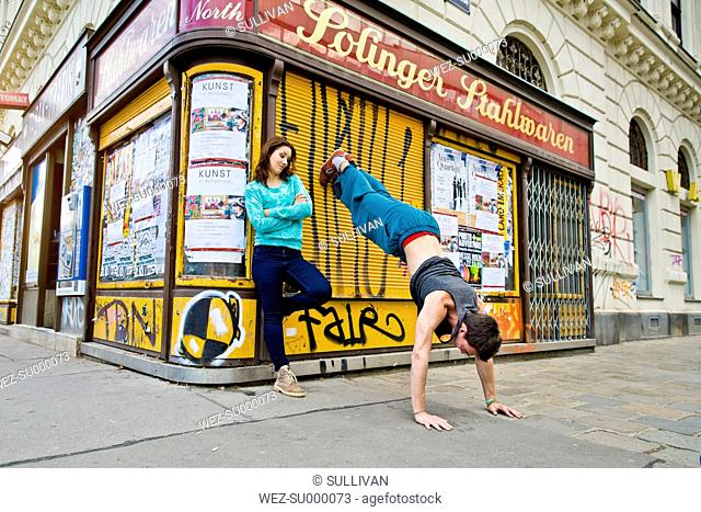 Young woman watching boyfriend doing a handstand