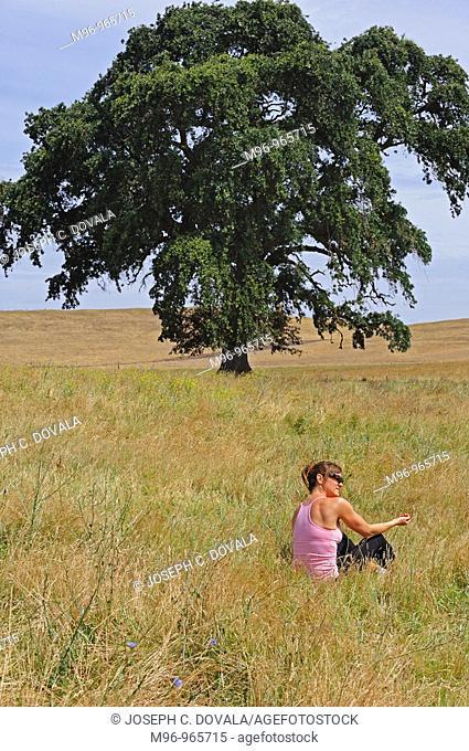 Woman sits in grass field by large oak tree, Oakdale, California, USA