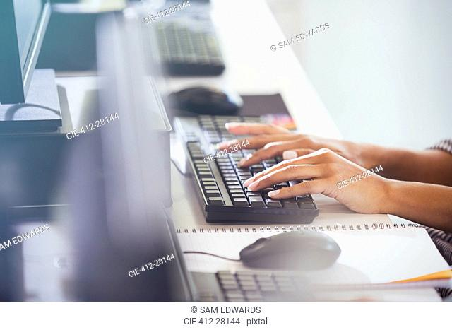 Student typing on computer keyboard in adult education classroom