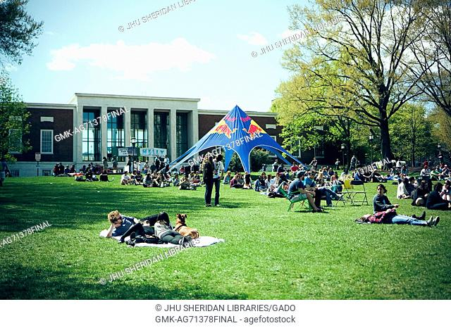 Several college students relaxing during Spring Fair, a student-run Spring carnival, on the Beach at Johns Hopkins University, 2015